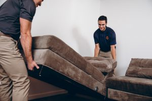 sewage cleanup professionals moving a couch out of harm's way