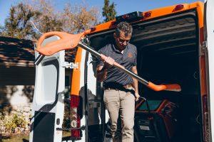 restoration technician carrying equipment out of van