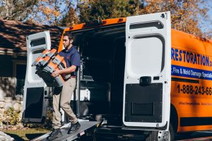 water damage restoration technician taking equipment out of van