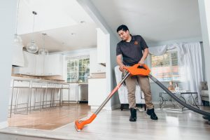 water damage restoration technician vacuuming water in home
