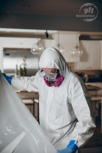 restoration technician taping off a section of a house for mold removal
