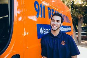 911 restoration professional in front of orange van